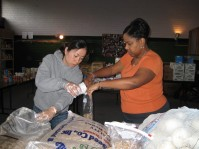 Takako Sophabmixay and Joyce Ester pack beans into smaller bags for families.